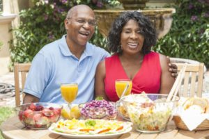 couple with dental implants enjoying summer foods outside